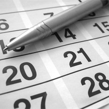 Black white photo of pen laying on calendar