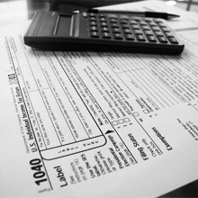 Black white photo of calculator laying on tax form