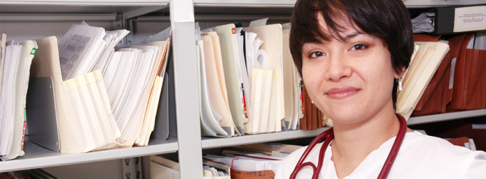 Nurse with stethescope standing in front of files